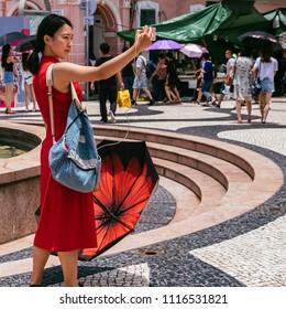 Macau, Macao Special Administrative Region of the People's Republic of China - June 2, 2018 : Largo de Senado (Senado Square), popular tourist attraction, a woman takes a selfie.