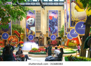 MACAU - OCT 18, 2014 : Photo of unidentified visitors are taking pictures at Dreamworks Experience at Cotal Strip Resort, Indoor Garden Decorations with Kungfu Panda and How to Train your Dragon Flags