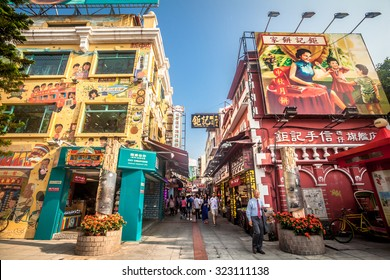Macau, Macau S.A.R. - September 19, 2015: Tourists and shoppers walking along a narrow street with colourful building in central Macau with many shops and restaurants. This street call food street.