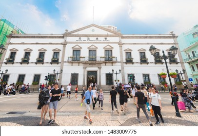 MACAU - SEPTEMBER 16, 2017: People stroll by the Civic and Municipal Affairs Bureau (Portuguese: Instituto para os Assuntos Cívicos e Municipais). Macau is a casino resort city in Southern China.