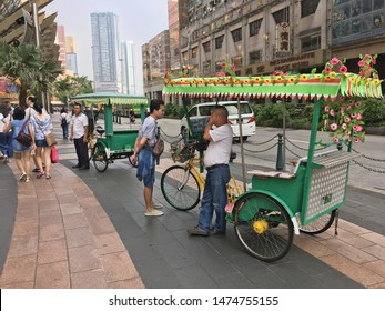 MACAU - SEPTEMBER 16, 2017: Unidentified rickshaws stand on pavement downtown the city. Macau is a resort city in Southern China known for its casinos and luxury hotels.