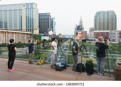 MACAU - SEPTEMBER 16, 2017: Unidentified photographers shoot the Venetian Macao hotel and casino resort at sunset.