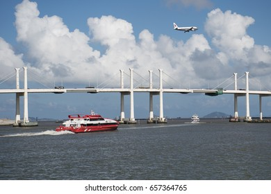 Macau-June 7: speed boat ferry services between Macau and Hong Kong at Ponte da Amizade or Amizade bridge with airplane on the sky on June 7, 2017