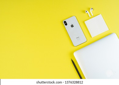 Macbook Air iPhone Xs Airpods on Yellow Layout Flat Lay. Kyiv Ukraine, 27 February 2019 Smartphone and Earphone on Freelance Business Workspace Background. Corporate Workplace Inspiration Top Flatlay