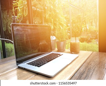 MacBook Pro on table wood  by the window and the sun on the morning of August 15, 2018, Bangkok, Thailand.