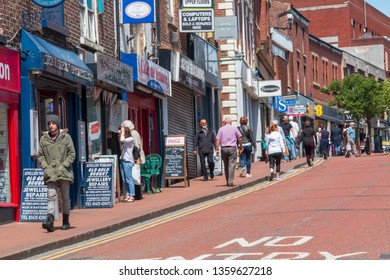 Macclesfield, Cheshire pedestrian street with shops and shoppers.  Signs outside the shops on a summers day. Macclesfield, UK June 4 2018