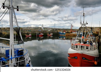 MacDuff, Aberdeenshire, Scotland, UK - June 17, 2018: Red and blue fishing boats and lighthouse at MacDuff Harbour Shipyards with view of Banff over Banff Bay Aberdeenshire Scotland UK