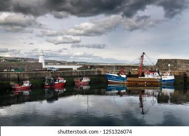 MacDuff, Aberdeenshire, Scotland, UK - June 17, 2018: Fishing boats and lighthouse at MacDuff Harbour Shipyards with view of Banff over Banff Bay Aberdeenshire Scotland UK