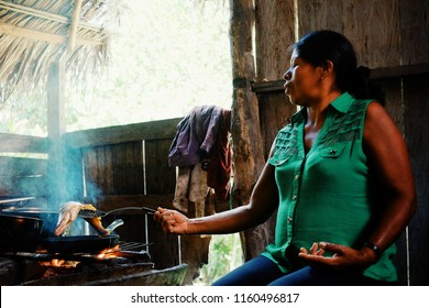 Macedonia, Amazonia / Colombia - MAR 10 2016: local ticuna tribal member woman cooking fish at their jungle rainforest home