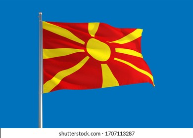 Macedonia national flag waving in the wind on a deep blue sky. High quality fabric. International relations concept.