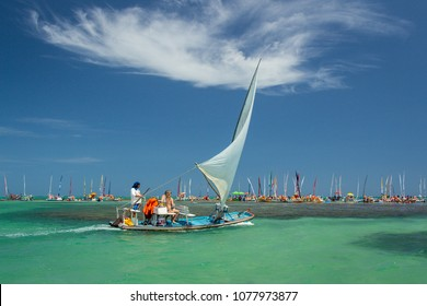 Maceio/Alagoas/Brazil - 01/04/2018: Traditional sailing boat (jangada) takes the tourists on a tour to see the corals on the beautiful Pajucara beach, with turquoise blue clear water.