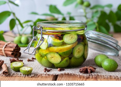 Macerating unripe walnuts, lemon and spices in alcohol in a jar, to prepare homemade tincture