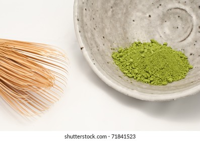 Macha green powder in a bowl, with the whisk