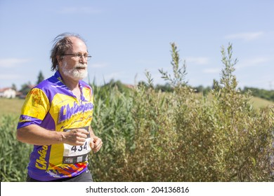 MACHILLY, FRANCE - JULY 6, 2014: Unidentified athlete participates in the running race of the Lake Machilly Triathlon which is part of the TriSaleve of Annemasse organization.