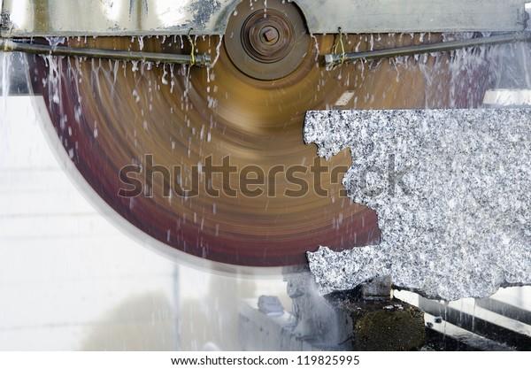 machine cutting a granite block