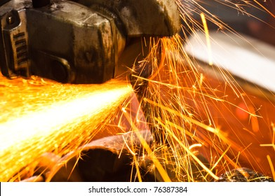 Machine cutting metal with sparks