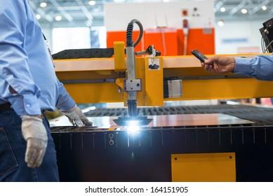 Machine cutting steel in a factory