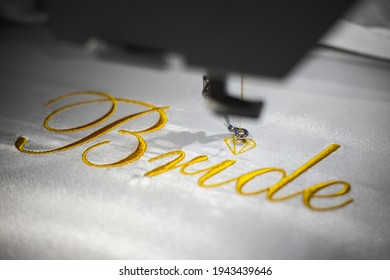Machine embroider the inscription bride on a white satin robe. Inscription bride with gold thread. Wedding day preparation. Elegant bridal lingerie.White accessories for the bride.Glamorous style.