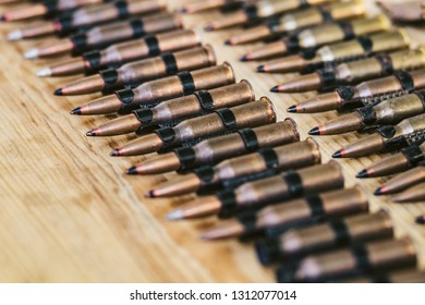 machine gun ammo on a wooden table, bullet belt, bandoleer, chain of ammo on wooden background,cartridge 7.62 mm caliber