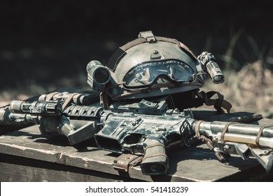 The machine,  machine gun, army helmet with a flashlight lying in a pile on a wooden box of ammunition. Conducting military operations.