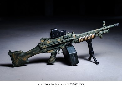 Machine gun with camouflage pattern on the ground on dark background/Machine gun on the ground