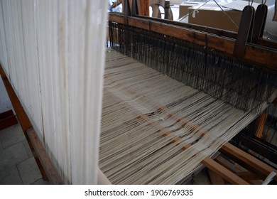 The machine is a hand-made wooden loom with threads for working on the machine. An old loom. Denizli. Turkey