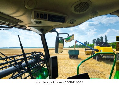 The machine for harvesting grain crops - combine harvester in action on rye field at sunny summer day. View from the combine cabin. Agricultural machinery theme.
