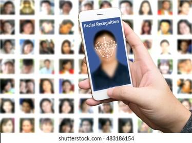 machine learning systems and accurate facial recognition concept , Man hand holding smart phone with blue screen and blur human faces background