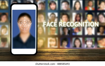 Machine learning systems and accurate facial recognition concept , smart phone on wood table with blue screen and blur human faces background
