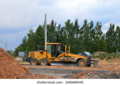 Сonstruction machine Motor Grader at a construction site level the ground and gravel stones for the construction of a new asphalt road. Road construction equipment