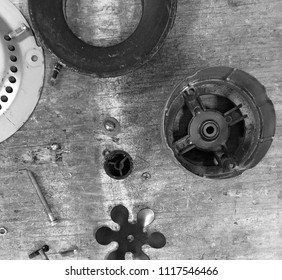 Machine parts lay flat on plywood work bench, black and white.