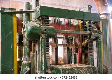 Machine sawing wood and sawdust flying