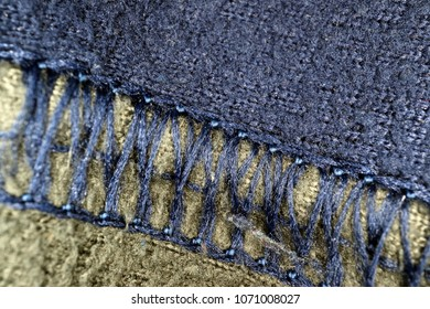 Machine stitched sewn seam between blue and grey synthetic fleece fabric. Extreme close up macro.