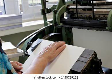 Machine for stitching book pages with threads in typography. Machine for sewing books and notebooks with threads. Women at work.