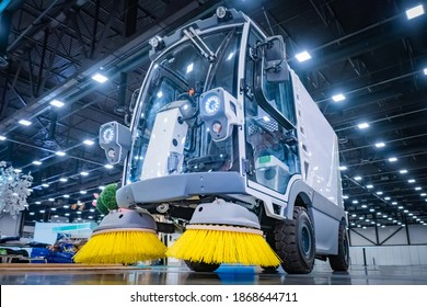 Machine for sweeping roads. Street cleaning vehicle. Demonstration of cleaning equipment at the exhibition. Machine with yellow cleaning brushes. Municipal utilities.