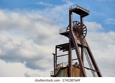 Machinery of an abandoned old coal mine against the sky with clouds.