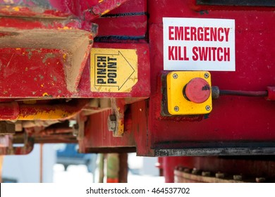 Machinery safety features - emergency kill switch and pinch point labels on a drill rig.
