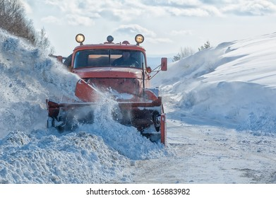 Machinery with snowplough cleaning road by removing snow from intercity highway after winter blizzard