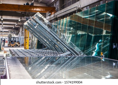 machines working with giant glasses in industrial glass window production factory. The machine is lowering the large glass.
