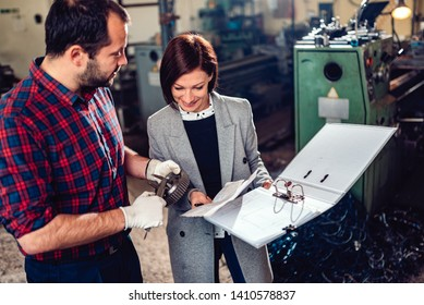 Machinist standing with female engineer and measuring cogwheel diameter with caliper at industrial manufacturing factory