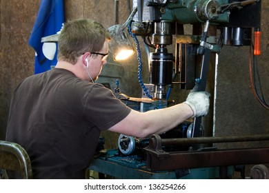 Machinist taps threads into steel using a drill press in production work in a metal shop.