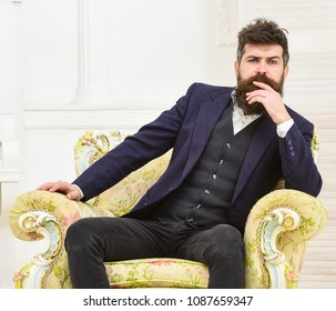 Macho attractive and elegant on serious face and thoughtful expression. Man with beard and mustache wearing classic suit, sits on old fashioned armchair, white background. Elite lifestyle concept
