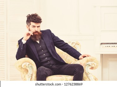 Macho attractive and elegant on serious face and thoughtful expression. Elite lifestyle concept. Man with beard and mustache wearing classic suit, sits on old fashioned armchair, white background.