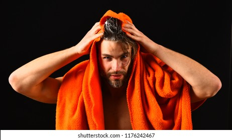 Macho attractive nude guy black background. Man bearded tousled hair covered with foam or soap suds. Wash off foam with water carefully. Man with orange towel ready to take shower. Water is over.