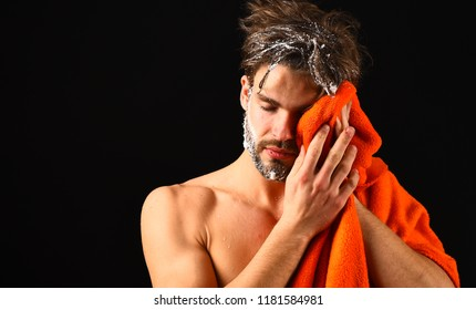 Macho attractive nude guy black background. Man bearded tousled hair covered with foam or soap suds. Wash off foam with water carefully. Man with orange towel wipe face, keep soap suds out of eyes.