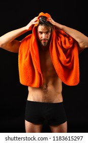 Macho attractive nude guy black background. Man bearded tousled hair covered with foam soap suds. Wash off foam with water carefully. Man with orange towel wipe hair. Apply conditioner after shower.