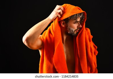 Macho attractive nude guy black background. Man bearded tousled hair covered with foam soap suds. Man with orange towel wipe hair. Wash off foam with water carefully. Apply conditioner after shower.