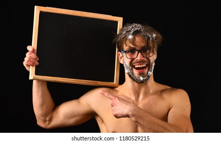 Macho attractive nude guy show blackboard. Man bearded tousled hair covered with foam wears eyeglasses. Lack of water. Need take shower. Man sexy muscular torso naked body hold blackboard copy space.