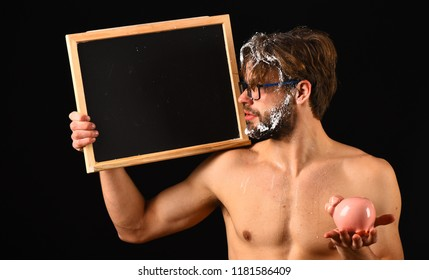 Macho attractive nude guy show blackboard. Expensive water tariff. Man bearded tousled hair covered with foam hold piggy bank. Lack of water. Need take shower. Man naked body blackboard copy space.