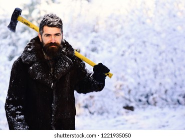 Macho with beard and mustache holds yellow ax. Frozen woodsman concept. Man in fur coat in the forest with axe on shoulder. lumberjack concept. lumberjack man working in the winter forest.